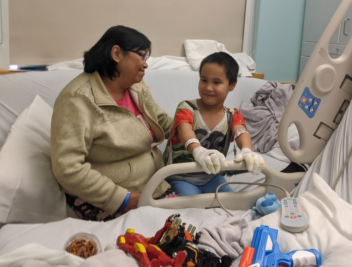 Irene Camille with her son, Ethan Camille, inside his hospital room at the Alaska Native Medical Center in Anchorage. (Greg Kim / KYUK)