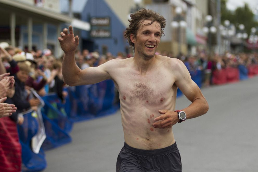 Nick Elson waves as he crosses the finish line in second place. (Sarah Bell / Alaska Dispatch News)