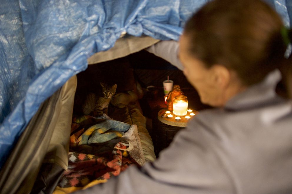 Judy Wurster, who has been homeless for threemonths, speaks to her cat, Sweetpea, in an encampment under Interstate 95 in Philadelphia, Jan. 4. (Mark Makela/The New York Times)