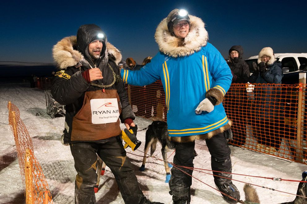 Richie Diehl and Matthew Failor greet each other after battling it out for second place in the last twenty-miles of the Kuskokwim 300. Failor pulled ahead towards the end of the race, beating Diehl by 2 minutes. (Katie Basile / KYUK Public Media)