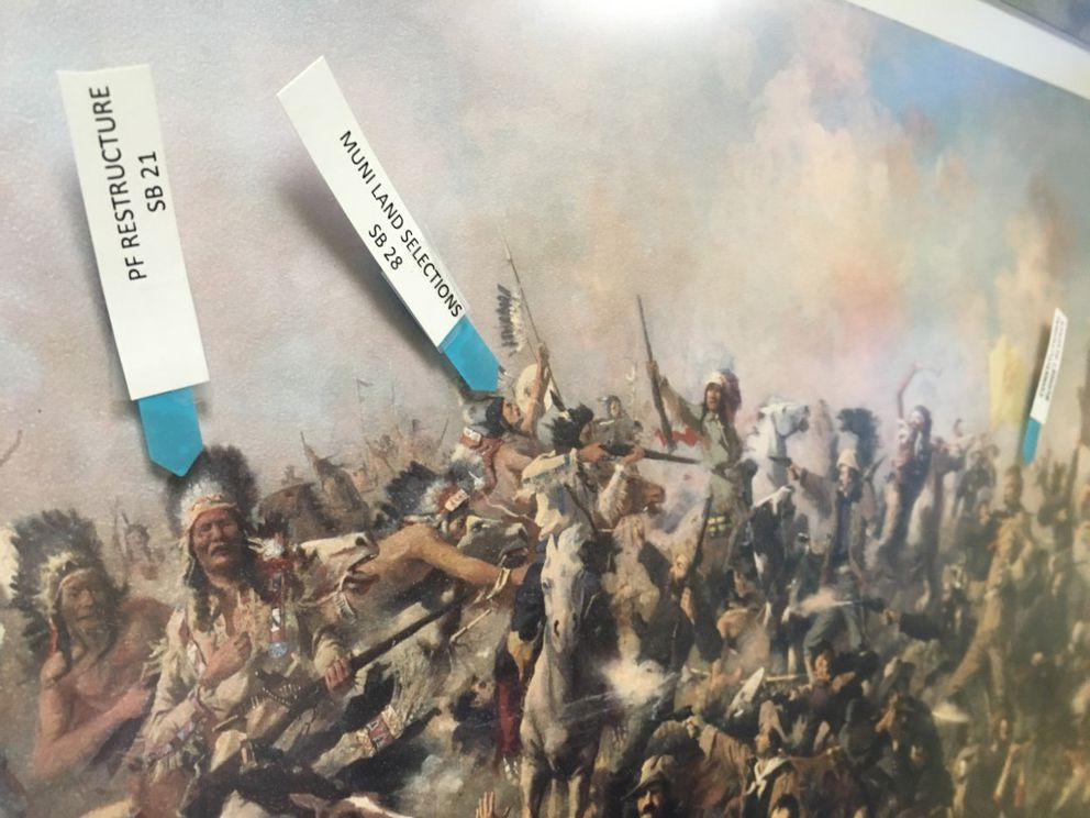A painting of the Battle of Little Big Horn in the office of Sitka Republican Sen. Bert Stedman, isused by the senator as a scoreboard, labeling its imageswith bill numbers. SB 21 is Stedman's bill to use Permanent Fund income for state revenue, while SB 28 would grant additional state land to the Petersburg Borough. (Nathaniel Herz / Alaska Dispatch News)