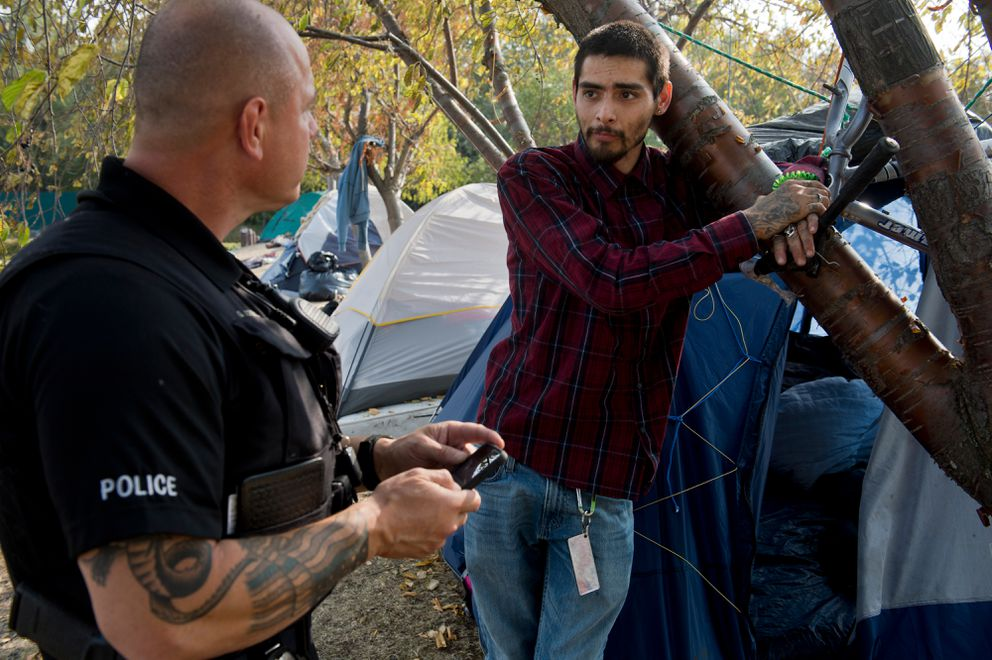 Anchorage Police Officer Gordon Korrell talks with Christopher Thompson at a camp located near 15h Avenue and A Street. (Marc Lester / ADN)
