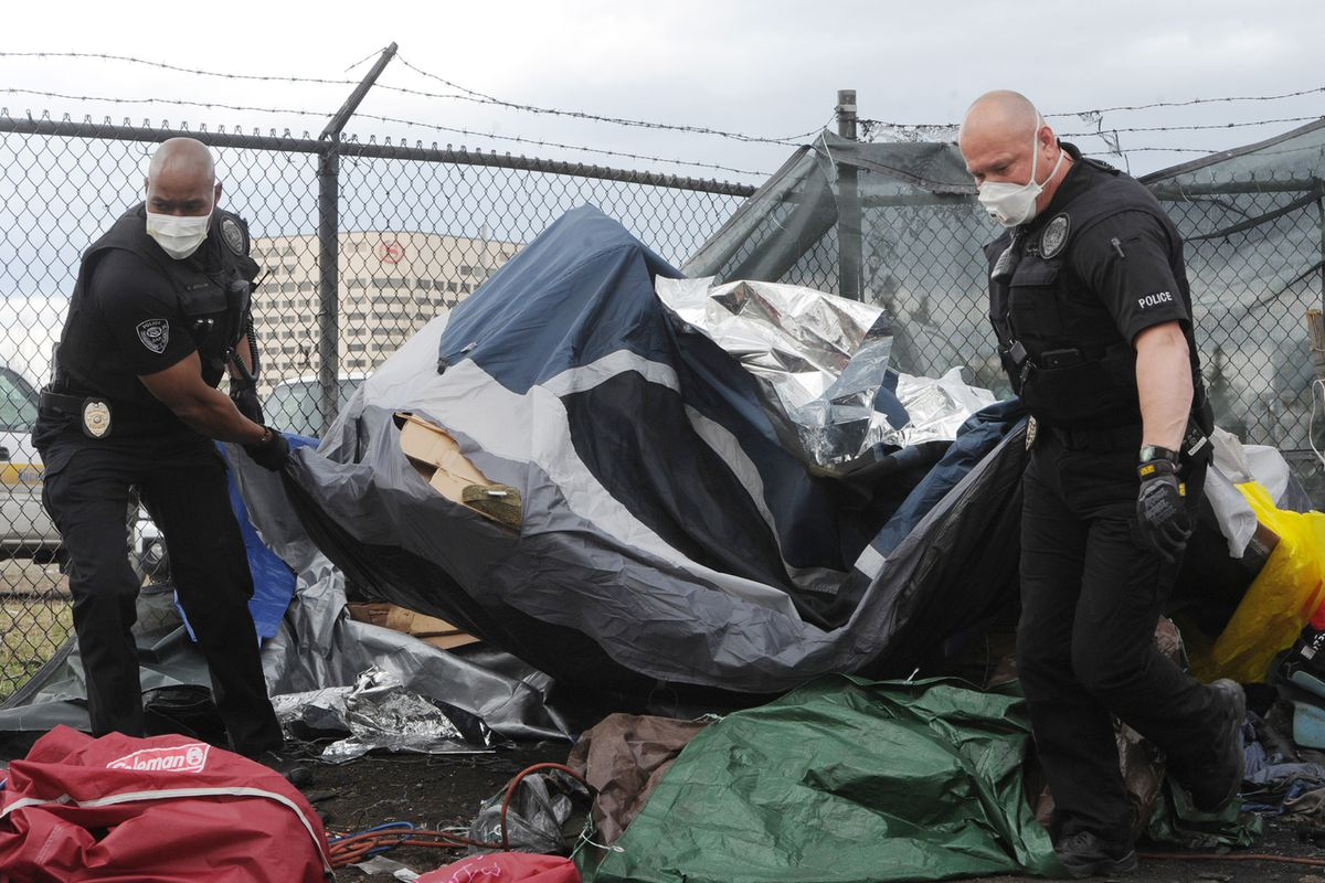 Anchorage Police Officers Damon Jackson, left, and Gordon Kovell remove a tent as officers with the community action policing team and Parks and Recreation workers removed and cleaned up an illegal homeless campsite near 3rd Avenue and Ingra Street on Monday, May 11, 2020. (Bill Roth / ADN)