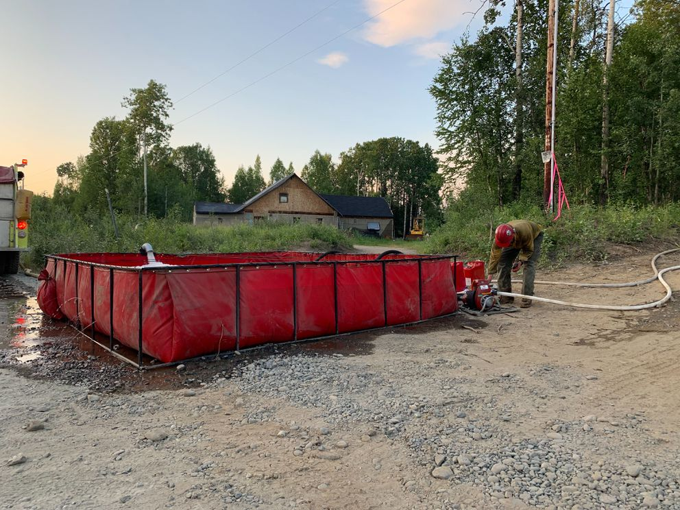 A firefighter adjusts the pump at a portable tank used to supply water to personnel attacking the Montana Creek Road fire, which was burning east of the Parks Highway and south of the Talkeetna junction on Wednesday, July 3, 2019. (Jeff Parrott / ADN)