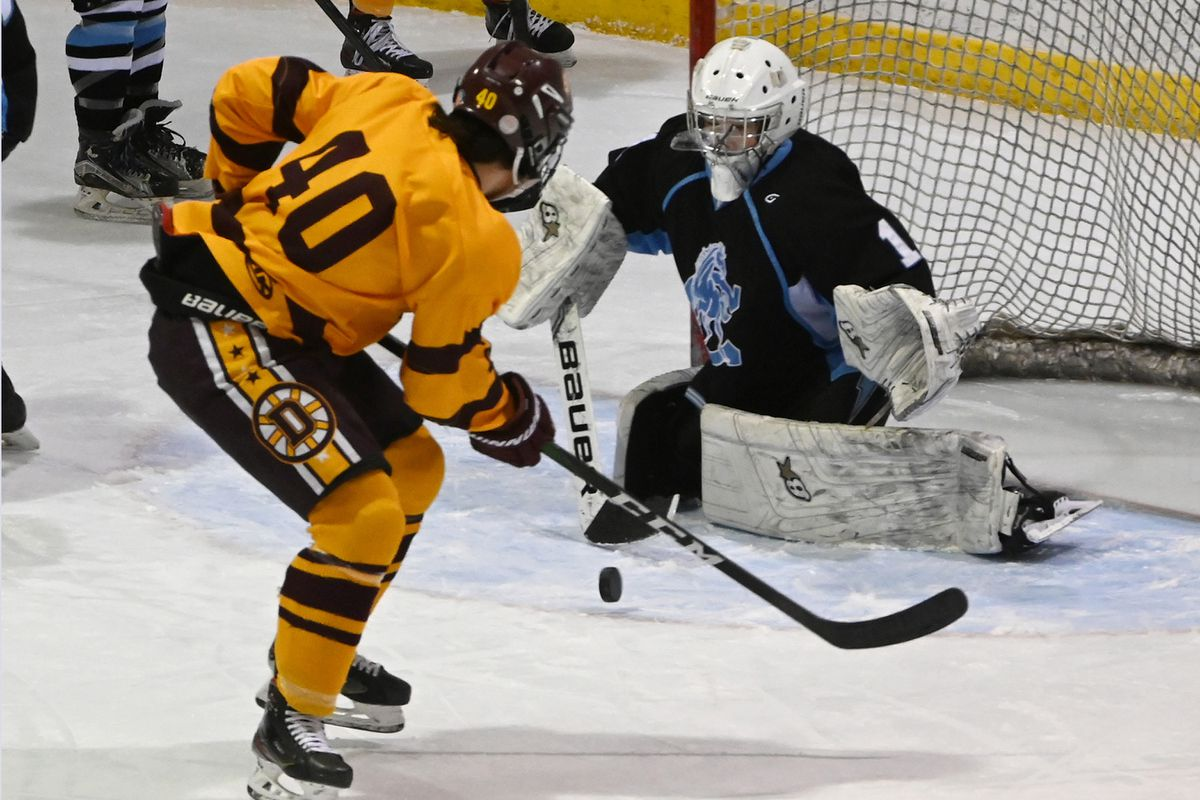 Chugiak goaltender Daegen Love stops a shot from Dimond forward Teague Porter during the first period at Ben Boeke Ice Arena on Tuesday. (Bill Roth / ADN)