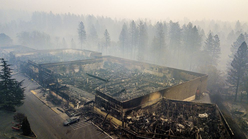 FILE - In this Thursday, Nov. 15, 2018 file photo smoke hangs over the scorched remains of Old Town Plaza following the wildfire in Paradise, Calif. Most homes are gone, as are hundreds of shops and other buildings. The supermarket, the hardware store, Dolly-O-Donuts & Gifts where locals started their day with a blueberry fritter and a quick bit of gossip, all gone. The town quite literally went up in smoke and flames in the deadliest, most destructive wildfire in California history. (AP Photo/Noah Berger, File)