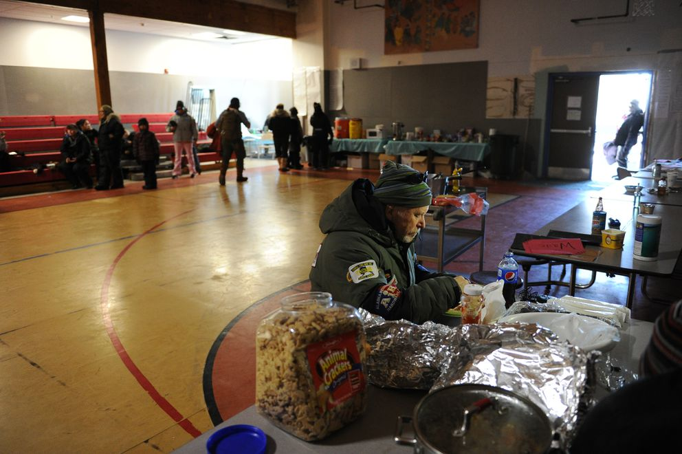 Jeff King has a hot meal while the container of animal crackers he brought as a gift for the village sits on the table of the Nulato checkpoint. (Bob Hallinen / Alaska Dispatch News)