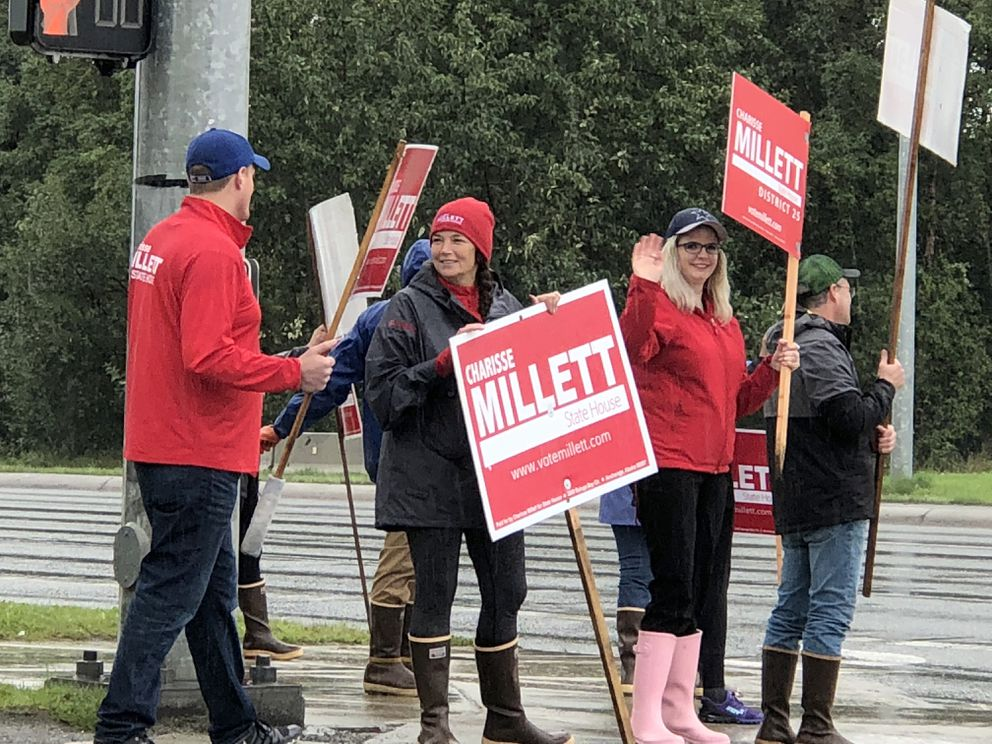 Charisse Millett (black coat, red hat) and supporters campaign and wave signs at the corner or Lake Otis and Dowling, on Tuesday afternoon, Aug. 21, 2018. (Loren Holmes / ADN)