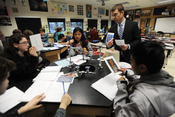 Ben Walker, a 7th grade science teacher at Romig Middle School, works with students after being named Alaska Teacher of the Year during a school assembly on Thursday morning, Oct. 12, 2017. (Bill Roth / Alaska Dispatch News)