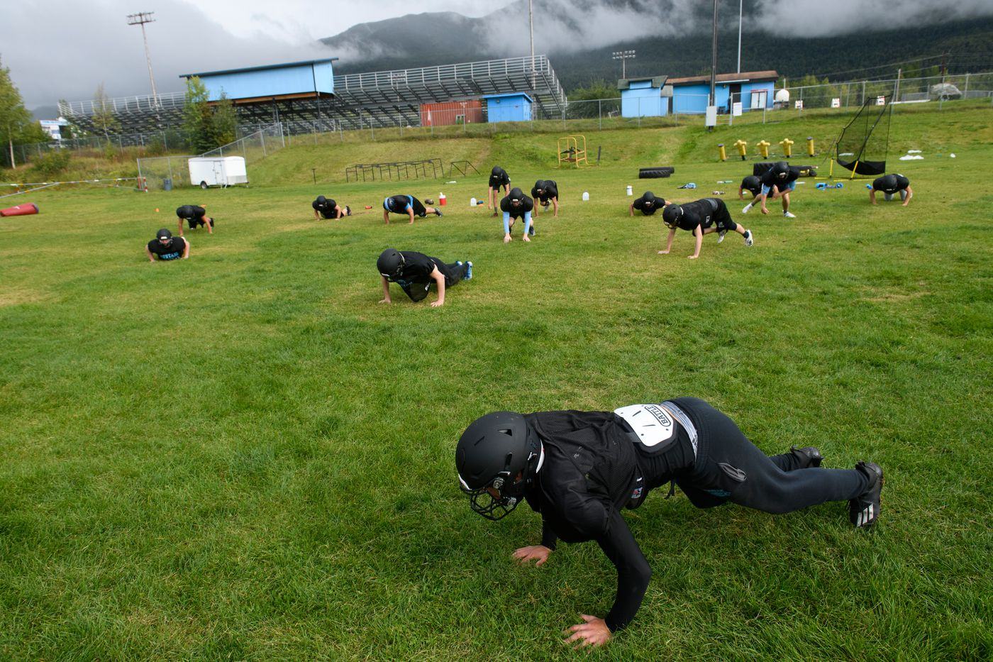 Chugiak players do burpees on orders from head coach Ryan Landers as a reminder to keep their distance from one another. (Marc Lester / ADN)