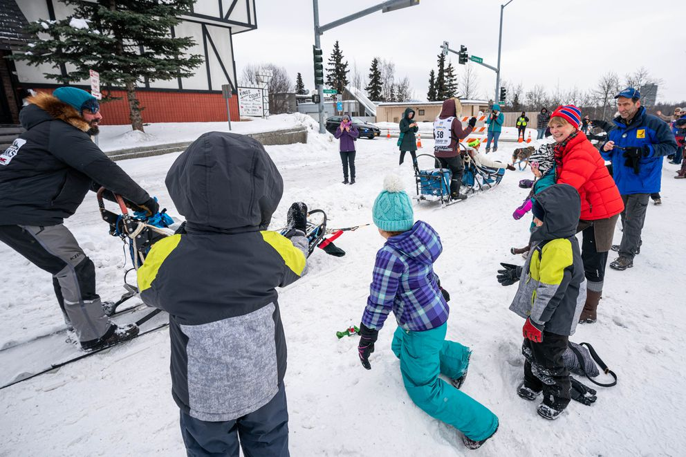The Leman family catches booties thrown by the last musher, Paige Drobny of Cantwell, to run the Iditarod Trail Sled Dog Race ceremonial start route on Saturday, March 7, 2020, in Anchorage. From left are Judah, 4, Ruth, 8, Isaac, 6, and Lydia, 3. (Loren Holmes / ADN)