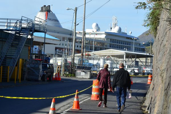 A pair of cruise ship passengers walk back to the Silversea cruise ship Silver Shadow Wednesday, Sept. 18, 2013. Passengers from the ship, the last to visit Kodiak this year, were the first to use Kodiak's new $2.8 million sidewalk, which stretches 1,100 feet from City Pier 2 to Jack Hinckel Way, about one-third of the distance between the pier and downtown Kodiak. (AP Photo/Kodiak Daily Mirror, James Brooks)