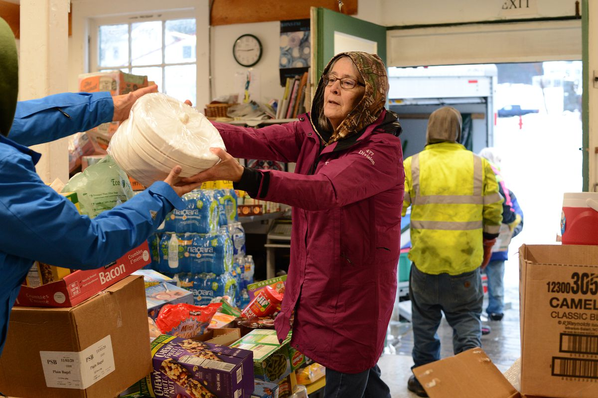 Kathy Berzanske passes a package of paper plates as she unloads a truck of relief supplies donated to Haines by Juneau residents on Sunday, Dec. 6, 2020. (James Brooks / ADN)