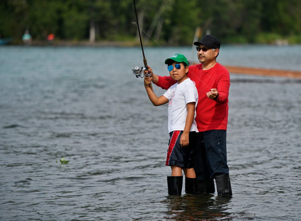 Olin Napoleon teaches his son Christian, 12, to cast while fishing on the Kenai River near the Russian River Ferry crossing on Thursday, July 18, 2019. Both are from Anchorage. (Marc Lester / ADN)