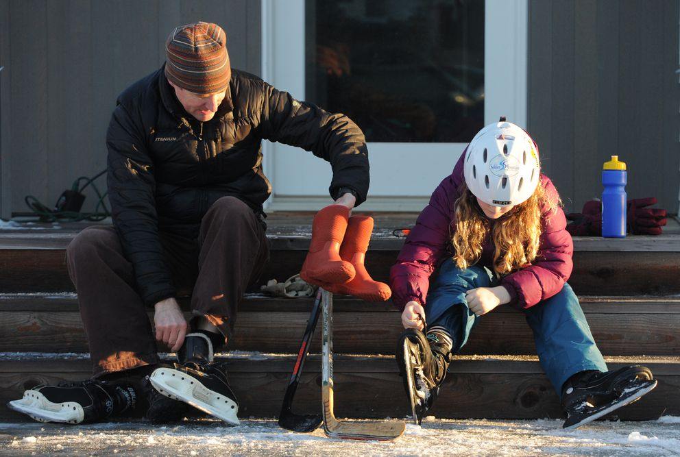 Grant Crosby and his daughter Hella Crosby, 8, take of their hockey skates while sitting on their porch after skating on the icy streets near downtown Anchorage on Sunday, Dec. 8, 2019. (Bill Roth / ADN)