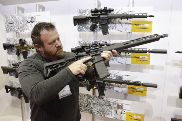Bryan Oberc, Munster, Ind., tries out an AR-15 from Sig Sauer in the exhibition hall at the National Rifle Association Annual Meeting in Indianapolis, Saturday, April 27, 2019. (AP Photo/Michael Conroy)