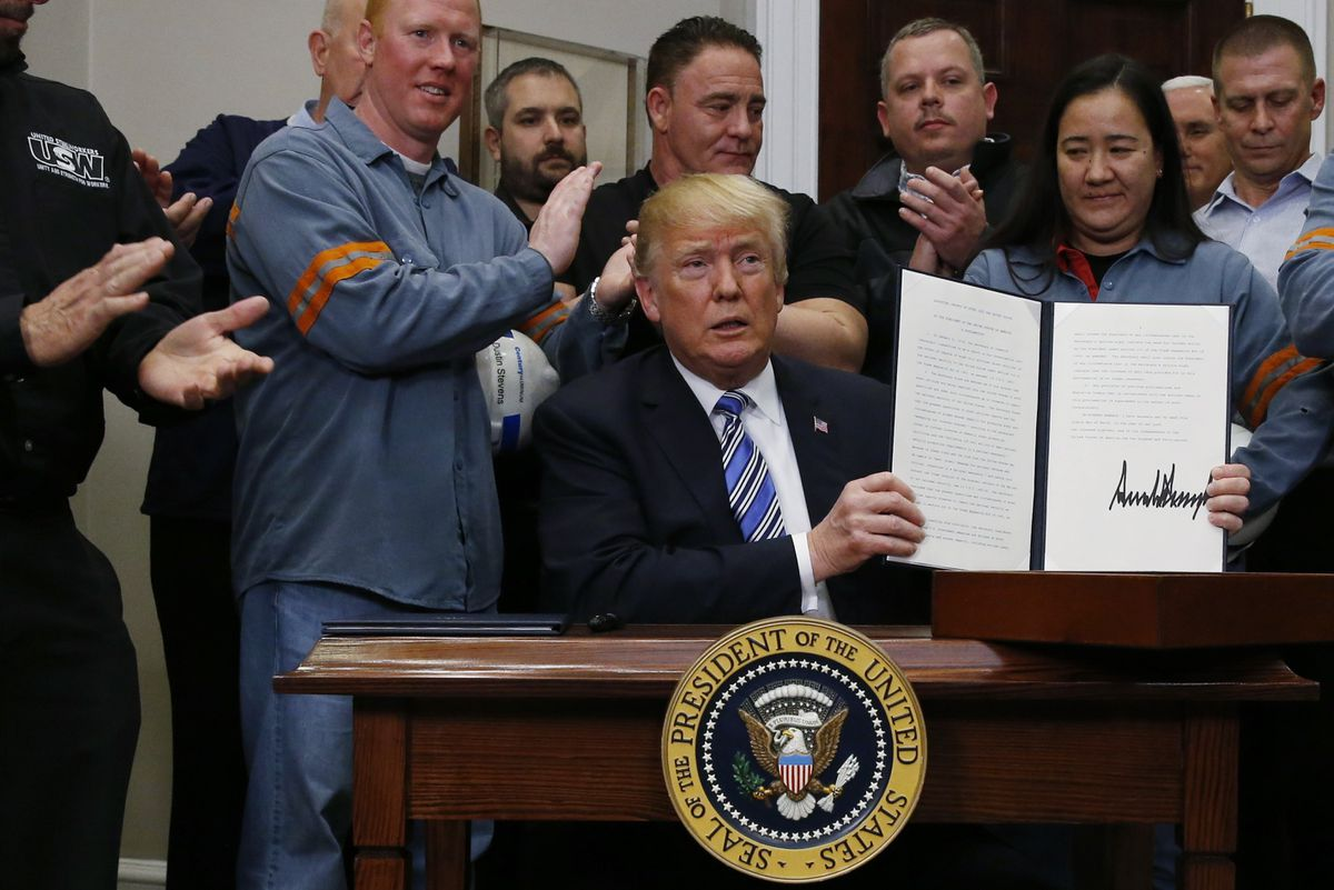 President Donald Trump holds up a proclamation during a White House ceremony Thursday establishing tariffs on imports of steel and aluminum. REUTERS/Leah Millis