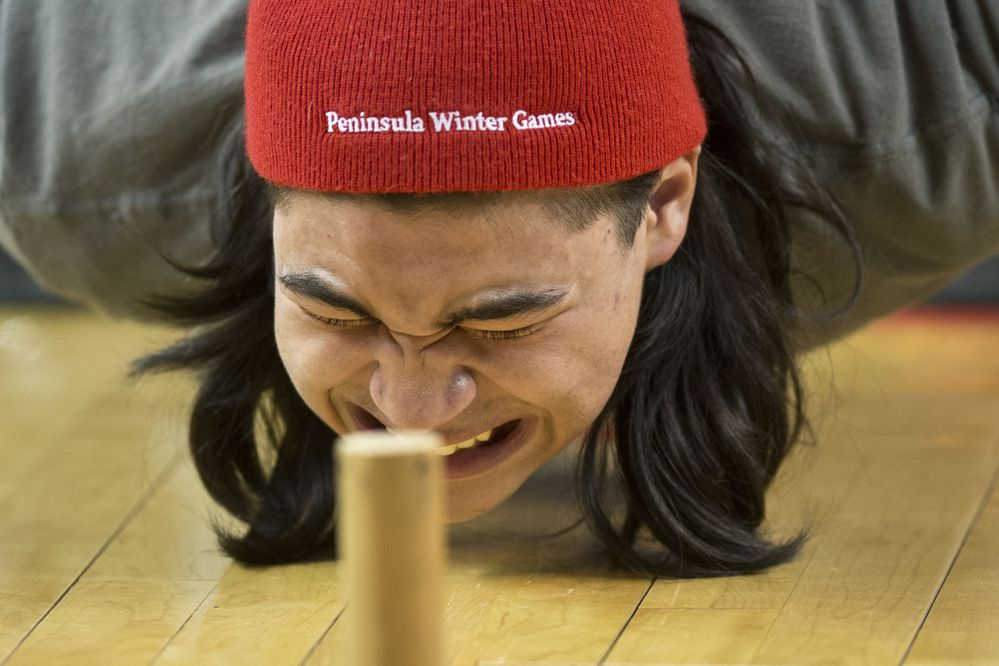 Nicholas Valenza, of Seward, strains to pull himself back up after placing the dowel in the bench reach competition at World Eskimo Indian Olympics on July 22, 2017. (Marc Lester / Alaska Dispatch News)