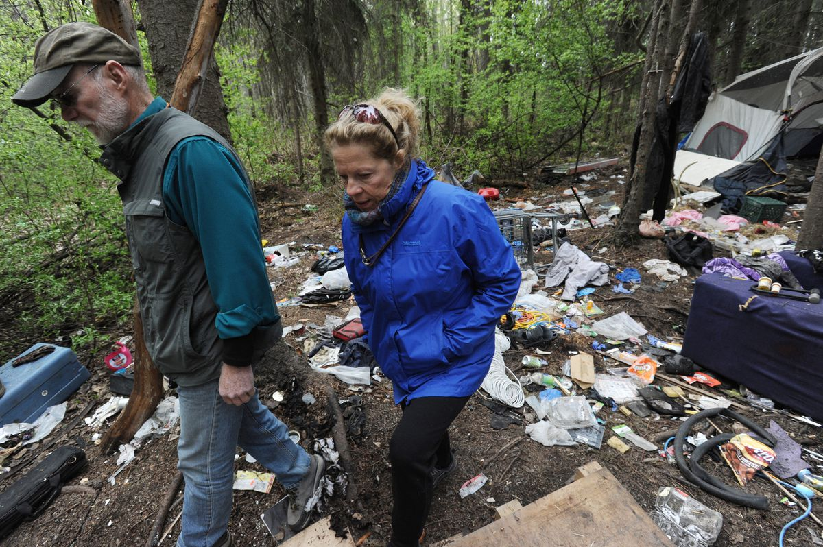 Russ Webb and Stephanie Rhoades pass through a homeless camp along the Chester Creek Trail in Anchorage on May 15.  (Bill Roth / ADN)