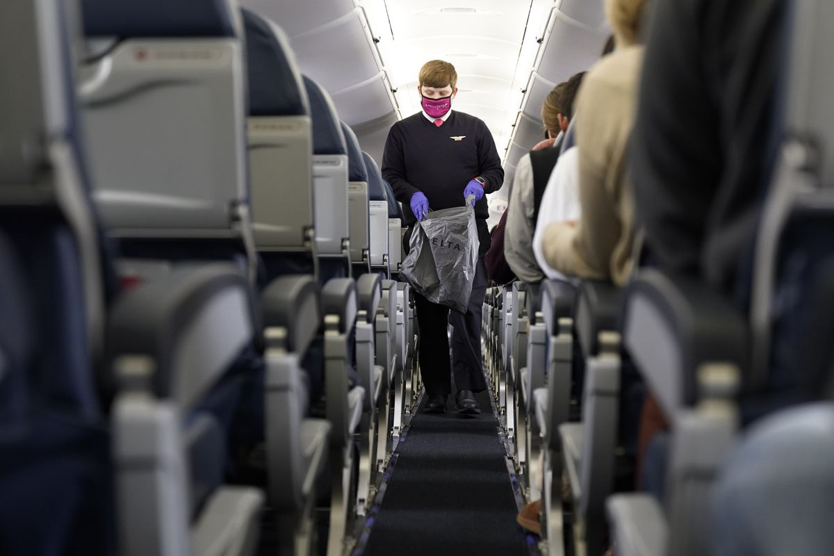 A Delta flight attendant works with a protective mask and gloves during a flight to Philadelphia, Nov. 30, 2020. (AP Photo/Paul Sancya)
