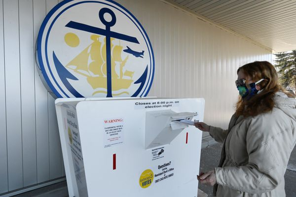 Cathy Steen drops her ballot envelope into a secure drop box at the Eagle River Town Center on election day during the regular municipal election on Tuesday, April 6, 2021. (Bill Roth / ADN)