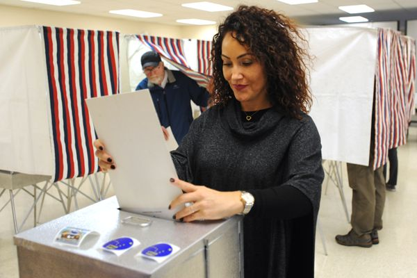Michelle Marshall places her ballot into a ballot box as Brad Owens exits a voting booth while early voting for the general election which began on Monday, Oct. 22, 2018. (Bill Roth/ ADN)