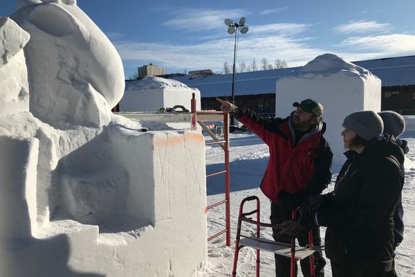 Wade Pier talks with teammates Marleigh and Dannielle Mellor Sunday, February 23, 2020, to prepare for the annual Fur Rendezvous' Alaska State Snow Sculpture Championship. (Tess Williams / ADN)