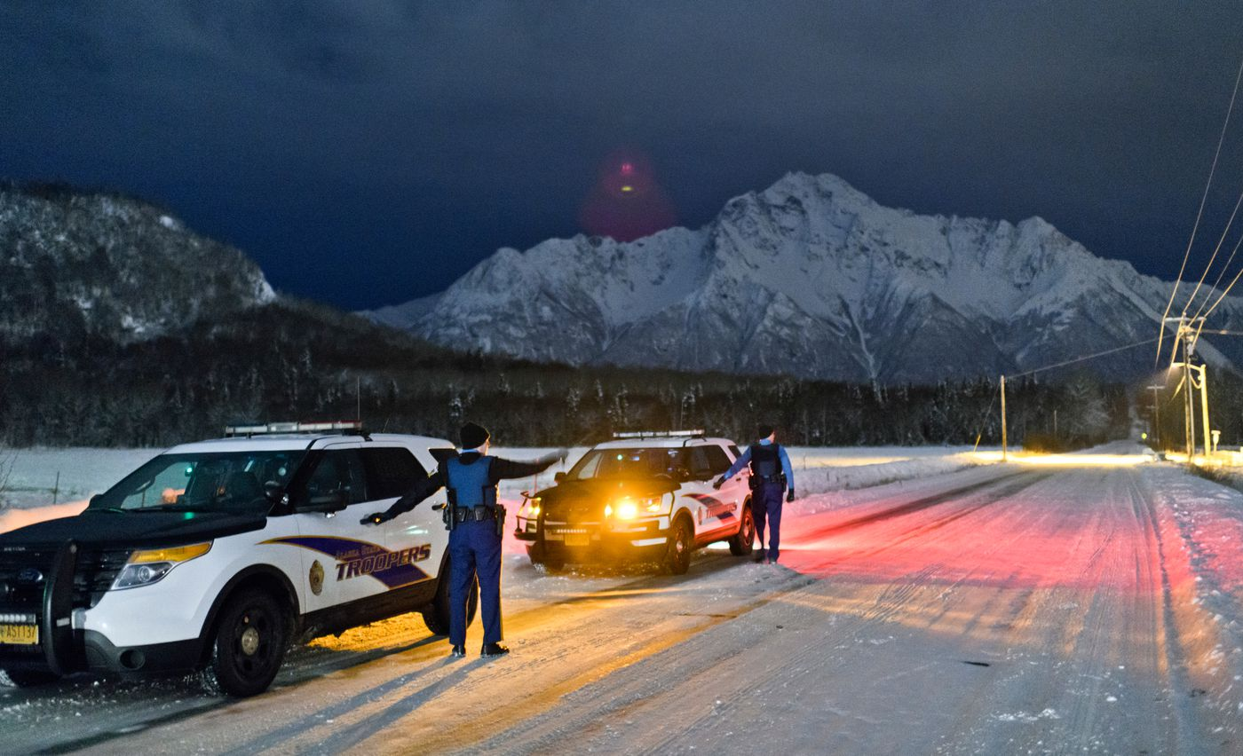 Alaska State Troopers Quinn Nardini, left, and Ryan Anderson talk on Bodenburg Loop, a street in Butte, while looking for a man who had created a disturbance at a nearby store on November 18, 2019. (Marc Lester / ADN)