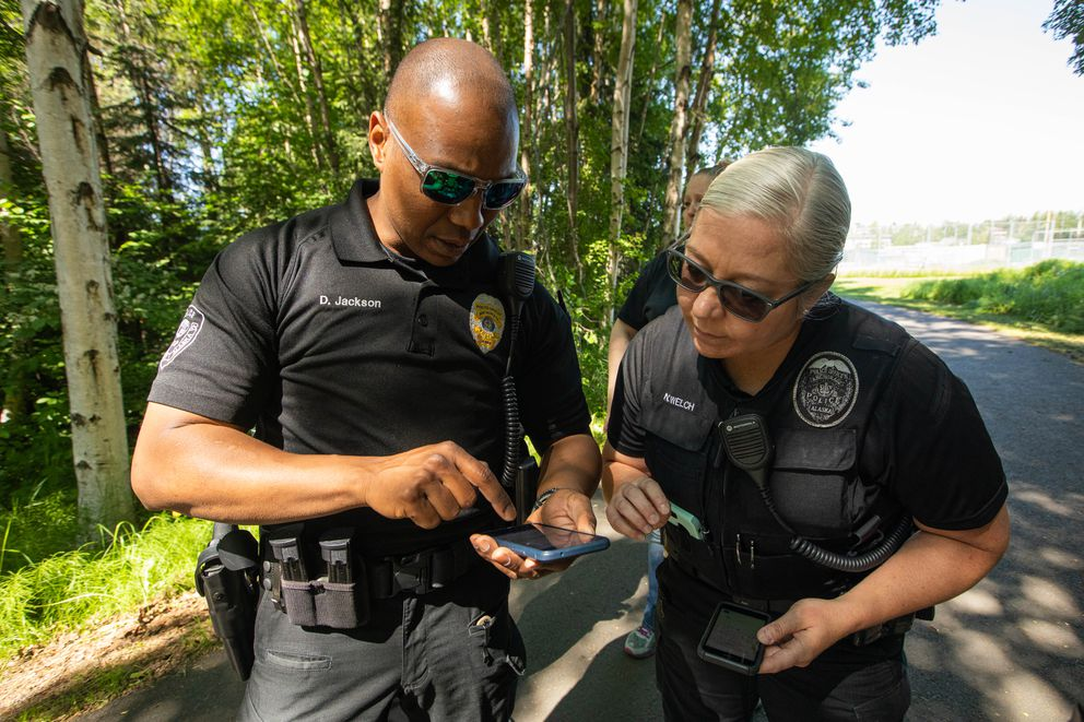 Officers Damon Jackson, left, and Natasha Welch look at a map showing the location of homeless camps Thursday, June 13, 2019 in the Chester Creek Greenbelt. (Loren Holmes / ADN)