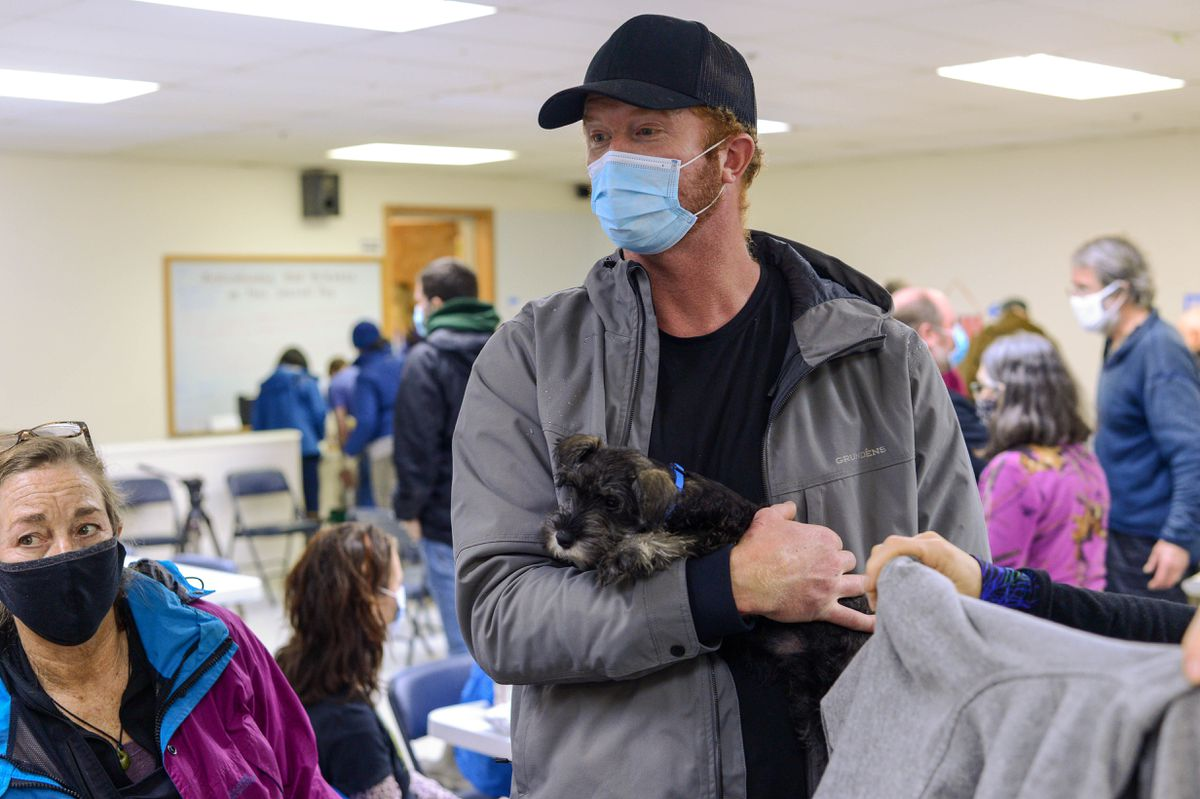 Ira Henry holds Snoop Dog as he talks to other evacuees during a lunchtime meeting on Saturday, Dec. 5, 2020, at Haines' American Legion Hall, which has served as a hub for evacuees after landslides and flooding over the past week. (James Brooks / ADN)
