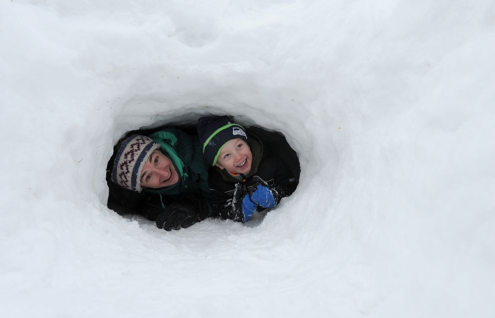 Naomi Tomco and her son Blake Tomco check out a snow cave during the Winter Trails Day at the Bureau of Land Management Campbell Creek Science Center in Anchorage on Jan. 28, 2017. (Bob Hallinen / Alaska Dispatch News)