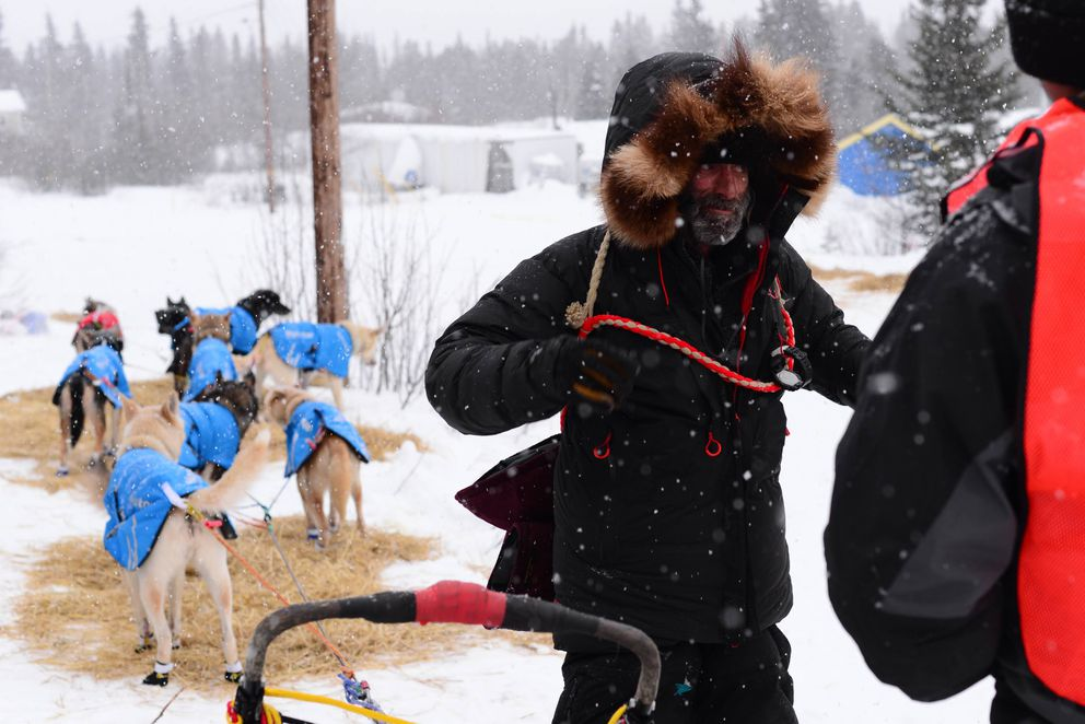 Tony Browning, who has run 14 Kobuk 440s, talks to volunteer officials at the Ambler checkpoint after running to Ambler through wind and snow. (Photo by Berett Wilber)