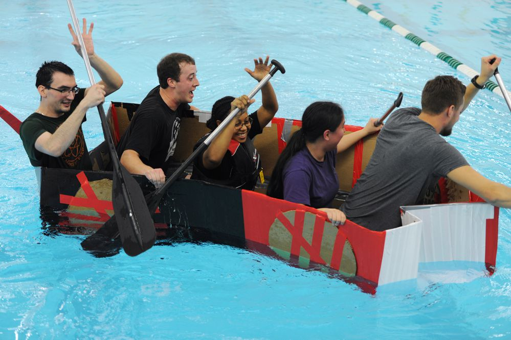 Five youth peer mentors paddle a cardboard boat designed by Alaska Native Science & Engineering Program students from the Lower Yukon and Lower Kuskokwin School Districts during a boat race at the UAA pool on Tuesday, Dec. 5, 2017. ANSEP middle school students participating in the first winter STEM Career Exploration session used science and math while designing their cardboard boats. (Bill Roth / ADN)