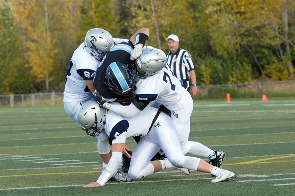 A gang of Eagle River tacklers converge on Chugiak quarterback Quentin Wilson during the Wolves' 34-21 high school football win over the Mustangs on Saturday, Sept. 22, 2018 at Tom Huffer Sr. Stadium in Chugiak. (Matt Tunseth/Chugiak-Eagle River Star)