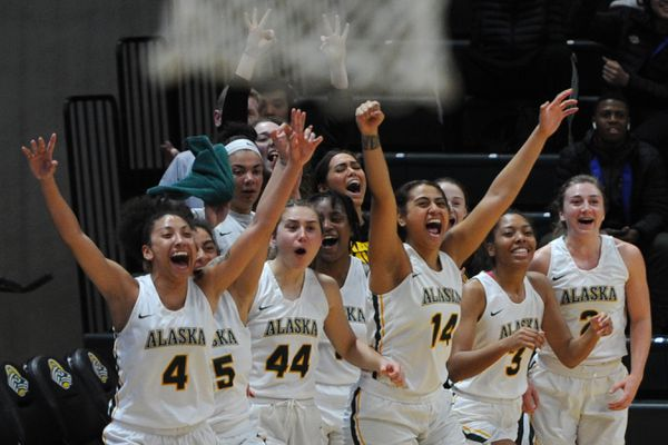 UAA players on the bench celebrate a three-point buzzer-beater by Yazmeen Goo to end the first half during the Seawolves' 79-52 home victory over the Concordia-Portland Cavaliers at the Alaska Airlines Center on Thursday, Dec. 5, 2019. (Bill Roth / ADN)
