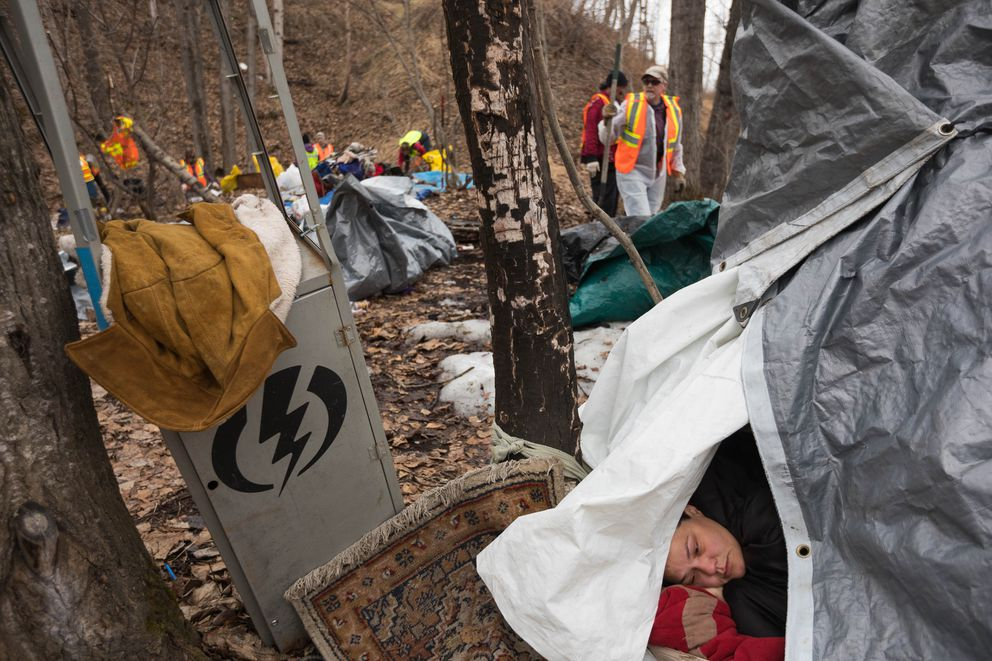 Amber Griffin lies in her shelter while volunteers pick up trash at a homeless camp near the Brother Francis Shelter on Saturday. Griffin said that she had moved to this spot a few weeks ago after being attacked at her old campsite. (Loren Holmes / ADN)