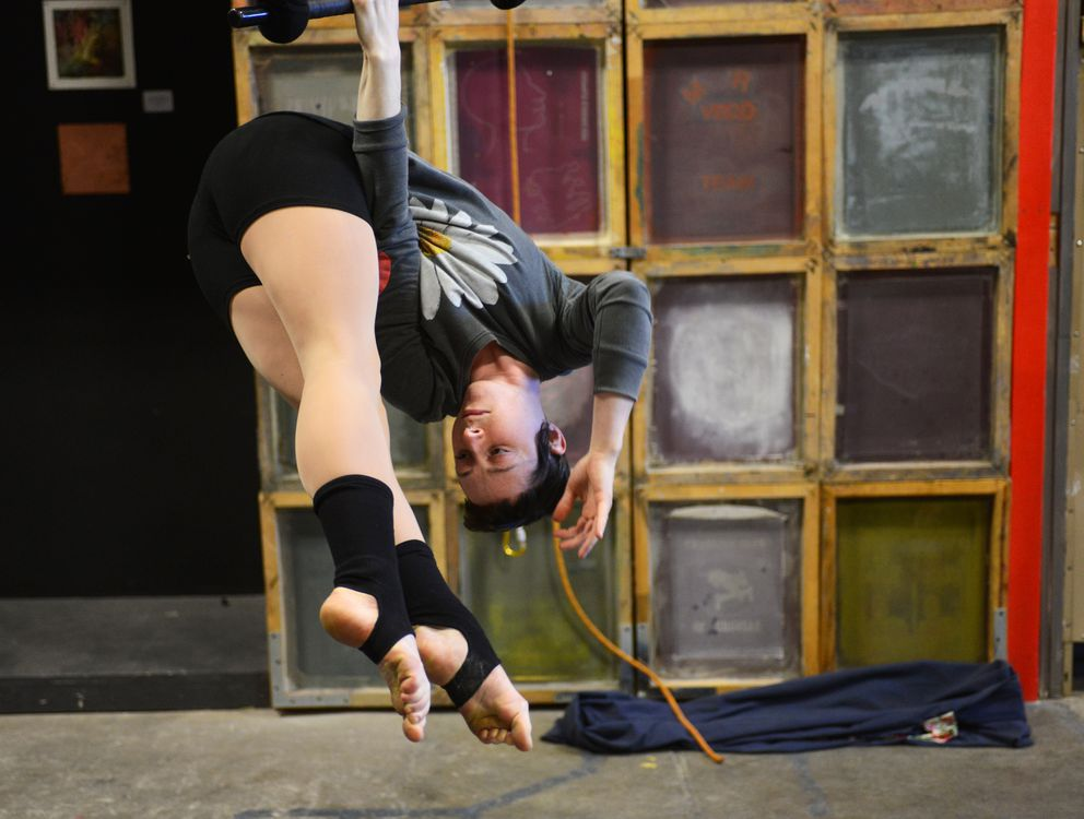 "Ariel Schmidtke hangs by one arm as she practices an excerpt from her show ""A Length of Rope"" on Thursday afternoon, March 16, 2017, at Anchorage Community Works in the Ship Creek area downtown. (Erik Hill / Alaska Dispatch News)"