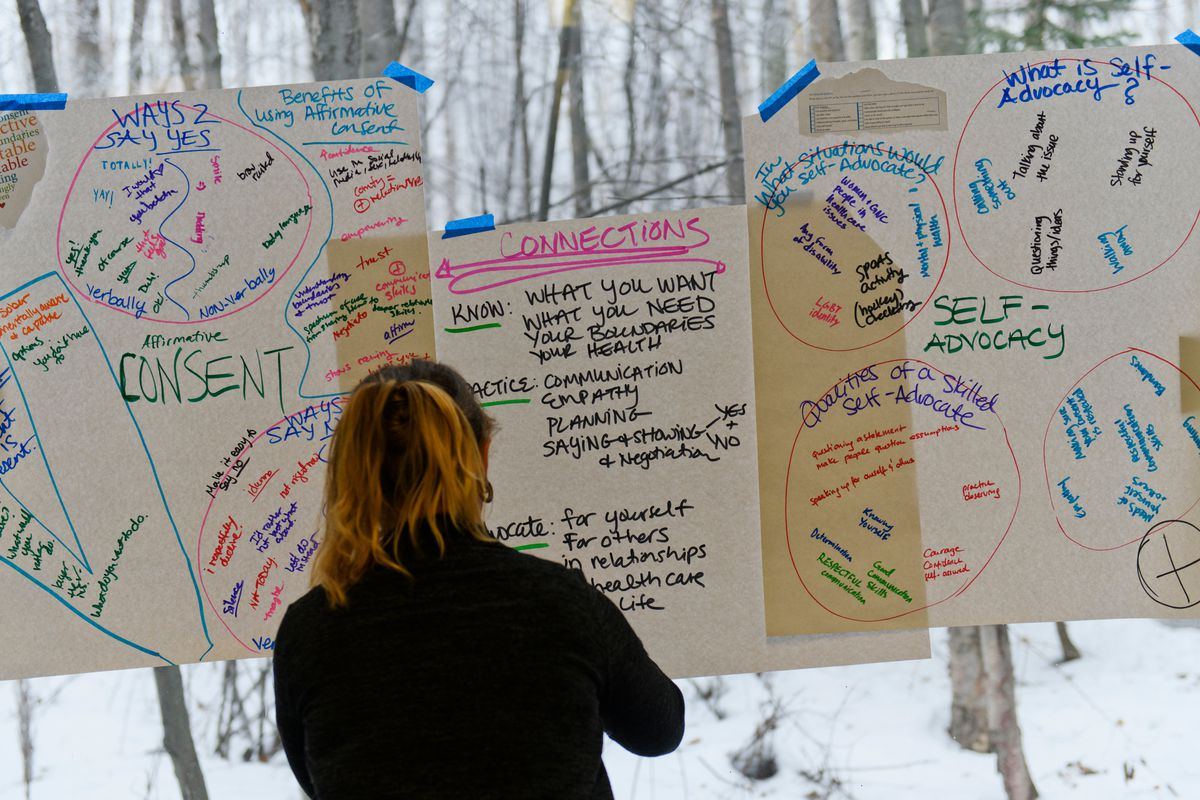 Jenny Baker, of Alaska's Adolescent Health Program, posts notes from discussion sessions on a window during the Youth Empowerment Party Monday. Dozens of teens and young adults gathered for the first Youth Empowerment Party, held at the BP Energy Center on January 21, 2019. (Marc Lester / ADN)