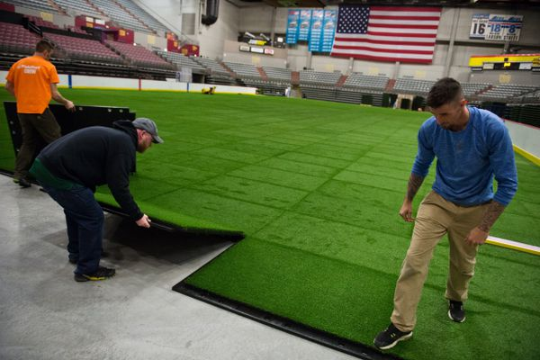 A new 100-by-200 foot artificial grass field was installed at the Sullivan Arena on March 12, 2018. The FieldTurf athletic field is made from snap-together panels made of shock-absorbing padding and designed to be easy to remove. From left are Kenyon DePriest of Palmer, Jack Nolan of Boston and Brian Garland of Maine. The turf field will first be used by an adult football league later this month. (Marc Lester / ADN)