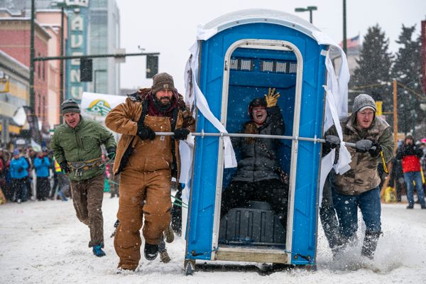 A team from Rent-A-Can, a portable toilet rental company, competes in the Fur Rondezvous outhouse races on Saturday, Feb. 29, 2020 in Anchorage. (Loren Holmes / ADN)