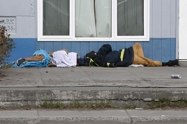 A pair of individuals sleep outside a church along Mt. View Drive on Wednesday, May 5, 2021. (Bill Roth / ADN)