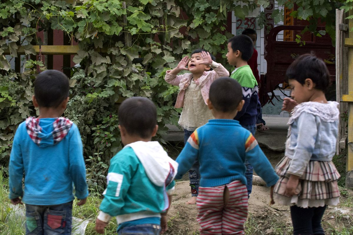 FILE - In this Aug. 30, 2018 file photo, Uighur children play outdoors in Hotan, in western China's Xinjiang region. (AP Photo/Ng Han Guan)