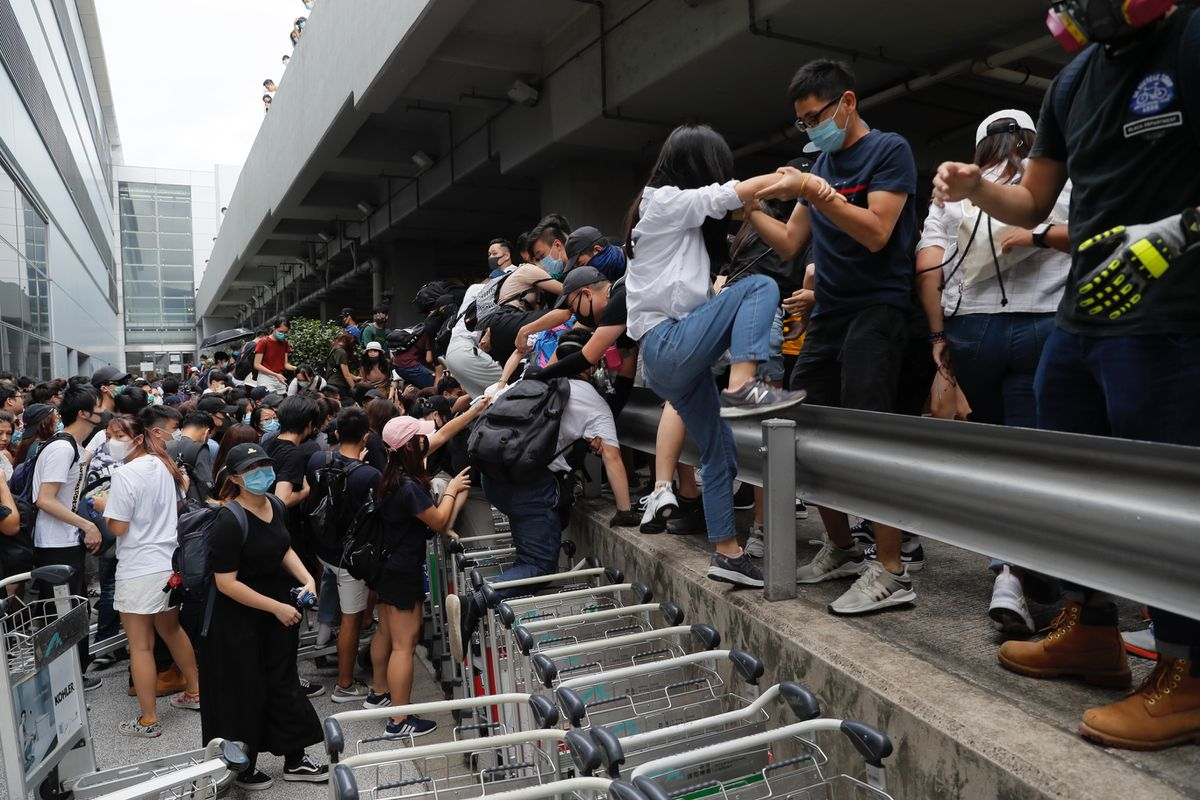 Pro-democracy protestors leave after riot police arrive outside the airport in Hong Kong, Sunday, Sept.1, 2019. The operator of the express train to Hong Kong's airport has suspended service as pro-democracy protesters gathered there following a day of violent clashes with police. Protesters gathered at the airport after online calls to disrupt travel. (AP Photo/Kin Cheung)