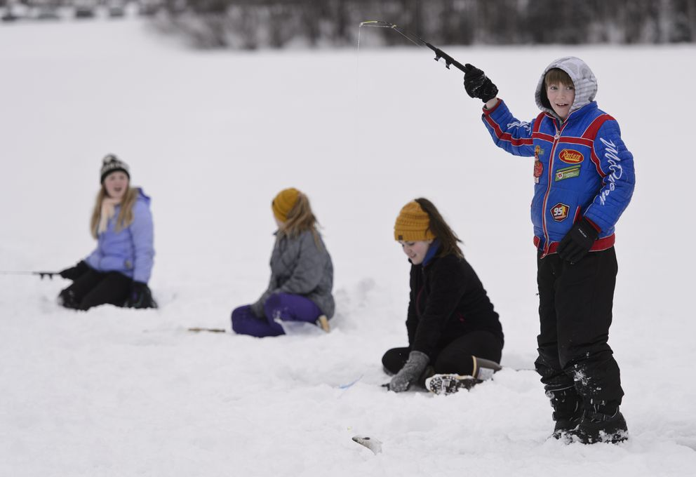 Walker Costello, right, of Eagle River Elementary School, pulls a fish from Jewel Lake. (Marc Lester / ADN)