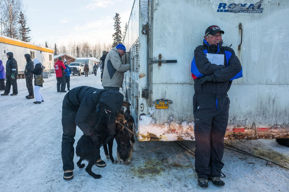 Florida veterinarian Norm Griggs takes shelter from the wind during the Iditarod vet checks in Wasilla on Wednesday. (Loren Holmes / Alaska Dispatch News)