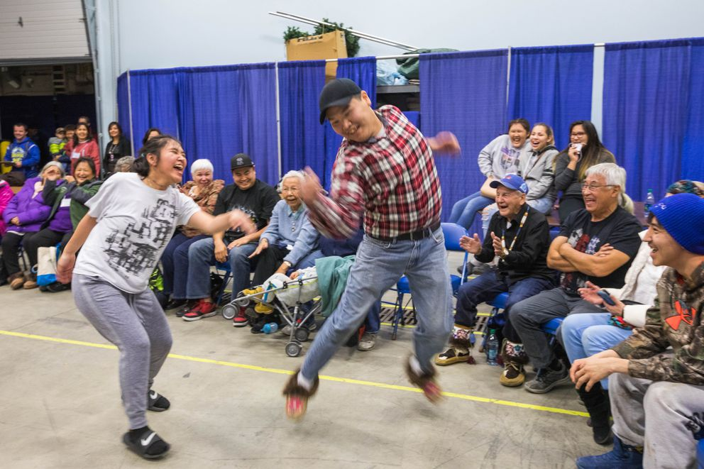 Jana Ticket, from Anaktuvuk Pass, tries to catch Anvik resident Isaac Ticknor as they dance the rabbit dance, a traditional Gwich'in fiddle dance, during a workshop on Tuesday. (Loren Holmes / Alaska Dispatch News)
