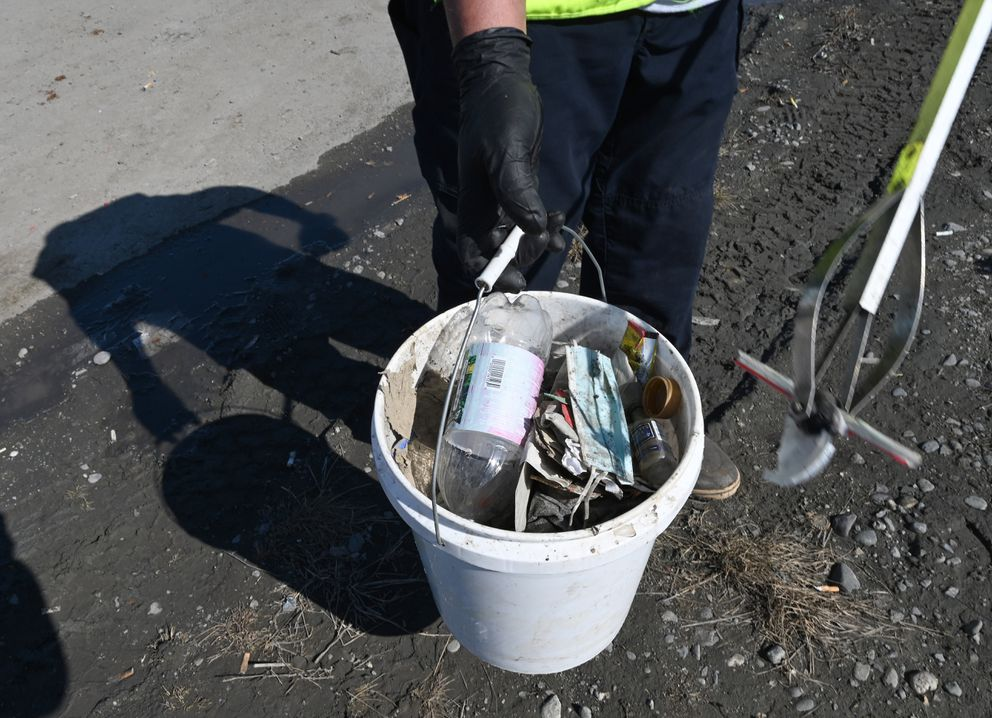 Ropati Nee Loa Kim picks up litter at the Ship Creek Small Boat Launch Wednesday April 21, 2021. He has worked for the munipality's Parks and Recreation department for about 9 years. (Anne Raup / ADN)