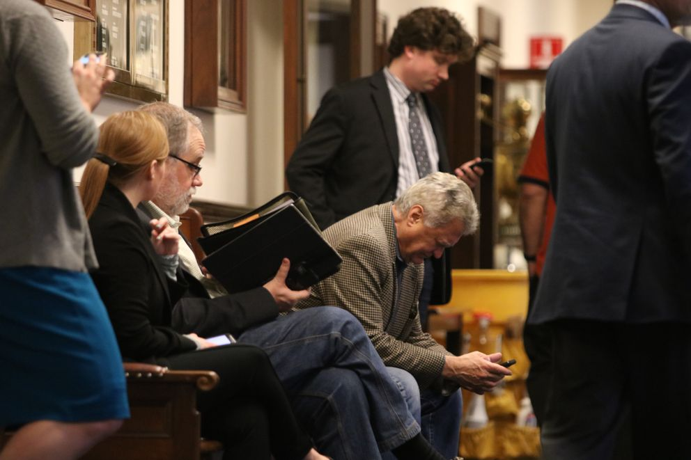 Lobbyist Bob Evans, leaning forward, checks his phone at the Alaska Capitol in Juneau on Saturday, May 12, 2018, with other lobbyists and legislative staffers nearby. It was a busy day for lobbyists at the Capitol, with an array of bills passing the House and Senate. (Nathaniel Herz / ADN)