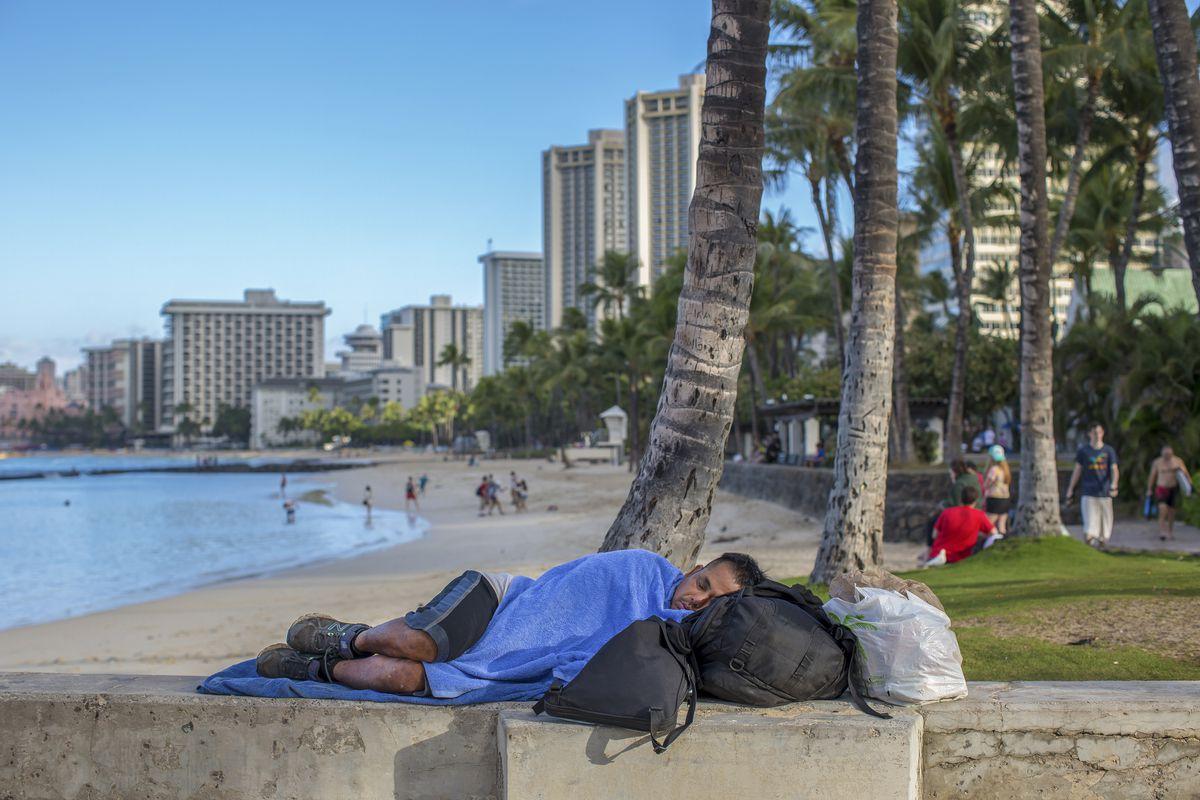 A homeless man sleeps near a pier on Waikiki Beach in Honolulu. (Monica Almeida/The New York Times)