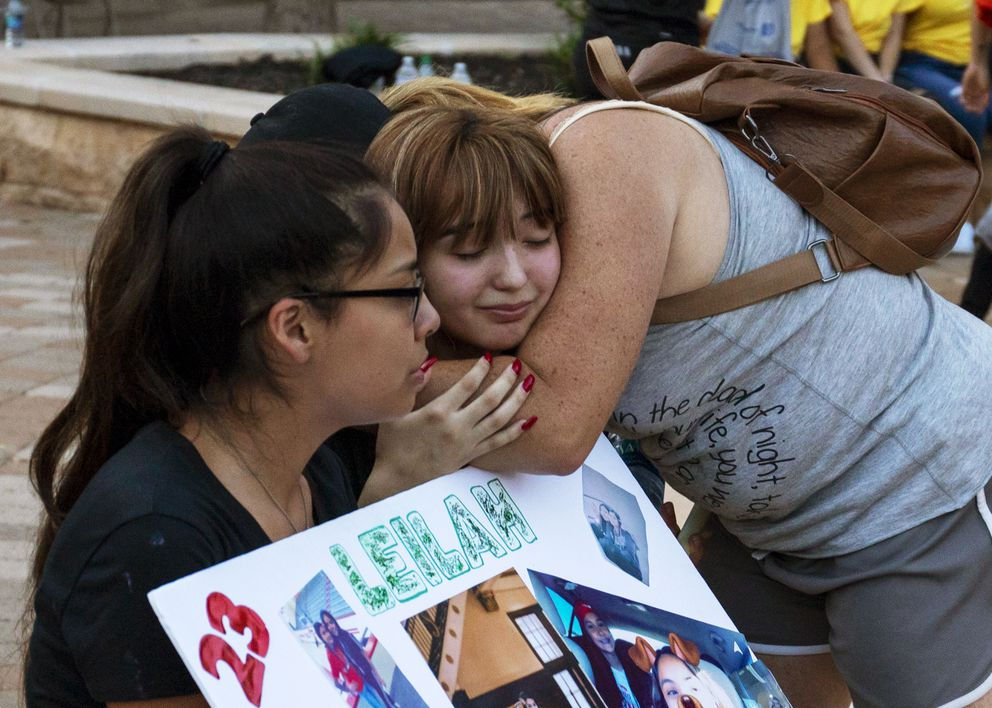Yasmin Natera and Celeste Lujan are embraced after a vigil for victims of a shooting spree the day before, Sunday, Sept. 1, 2019, at the University of Texas of the Permian Basin quad, in Odessa, Texas. (Jacy Lewis/Reporter-Telegram via AP)
